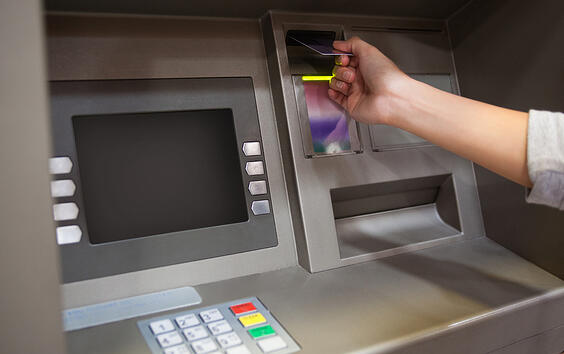 Hand inserting a credit card in an ATM